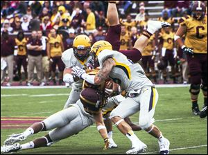 Toledo Rocket defenders tackle Central Michigan's Saylor Lavallii.