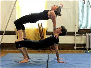 Toledo residents Charlie Westerink and Alyx Kendzierski practice during an acro-yoga class.