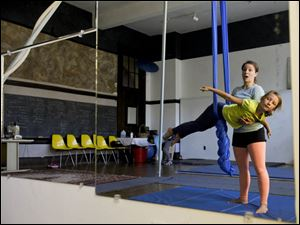 Instructor Emily Ellis holds Maya Stepnick, 8, of Toledo in a flying technique during a kids aerial silks class.