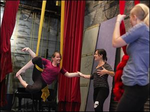 Amanda Knight of Lambertville, Mich., learns a flying technique as Instructor Erin Garber-Pearson of Toledo and Erica Horak of Swanton watch during a beginner aerial silks class.
