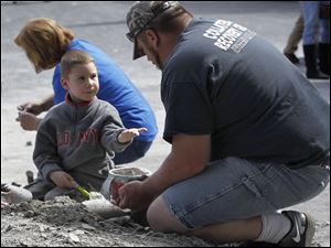 Xander Harloff, 5, works with Dave Wysong during the annual Fossil Fest. The Toledoans were strangers who paired up to find fossils in the rock pile.