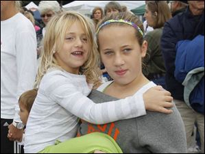 Hannah Hoverman, 10, of holds Tatum Takats, 5, while they watch the parade. They both live in Perrysburg.