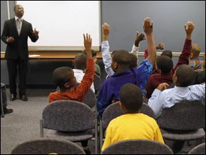 Boys raise their hands when the speaker, Glass City Youth minister Chris McBrayer, asked the question