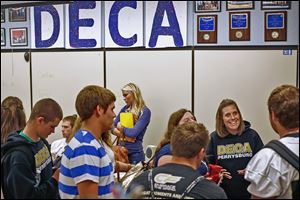Becky Byrd, right, jokes with one of her senior students  during DECA class at Perrysburg High School.