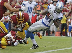 Detroit Lions wide receiver Calvin Johnson escapes the grasp of Washington Redskins inside linebacker London Fletcher and rolls into the end zone for a touchdown.