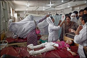 A Pakistani girl who was injured in a suicide attack on a church lies in a hospital bed surrounded by relatives and nurses. The twin suicide bomb attack killed dozens of Christians after worship on Sunday and injured scores. The assault was called the most deadly ever on Pakistan's Christian minority.
