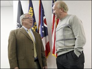 D. Michael Collins, left, speaks with Bruce Baumhower, right, president of Local 12, after accepting the UAW's endorsement for mayor.