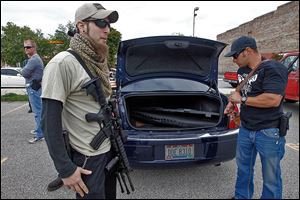Stephen Recknagel, left, of Toledo holds his AR-15 while friend Steve Stasa, right, from Holland, gets ready with an AK-47 to join Northwest Ohio Carry's open-carry walk.