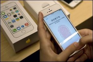 A customer configures the fingerprint scanner technology built into iPhone 5S at an Apple store in Wangfujing shopping district in Beijing.