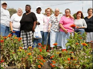 Left to right Cathy Jensen, Paula Unferdros, Geraldine Jacobs, Betsy Schuler-Oliver, Mary Fredericks, Lorece Brown, Daisy Davis, Judy Day, and Linda Columbi in the Lakewood Villas garden.