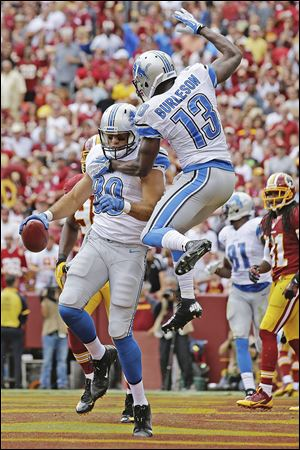 Lions tight end Joseph Fauria, right, celebrates his touchdown with wide receiver Nate Burleson in the first half against Washington on Sunday in Landover, Md. Burleson broke his arm in a single-car accident early Tuesday morning. Surgery is scheduled for today.