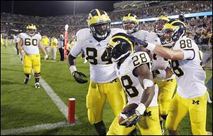 Michigan's running back Fitzgerald Toussaint, center, is congratulated by teammates after his fourth-quarter touchdown against Connecticut on Saturday.
