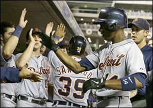 Detroit Tigers' Austin Jackson, right, is greeted in the dugout after his two-run home run off Minnesota Twins pitcher Scott Diamond in the fourth inning.