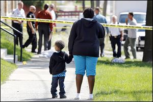 Deidra Hopings and her nephew Cross Hoffman, 3, watch as police investigate a shooting at 1520 Elm Street.