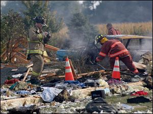 Firefighters search through debris after an explosion at a home on County Road 9, near County Road S, near Liberty Center.