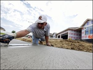A sidewalk gets shaped in front of new home construction in Omaha, Neb. in August.