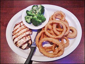 Grilled chicken breast with broccoli and onion rings.