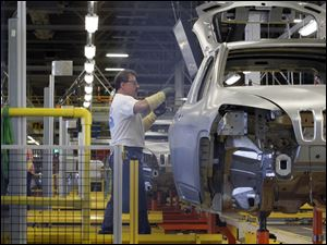 "An employee works on the new Jeep Cherokee line in the ""Body in White"" shop on July 18, 2013."