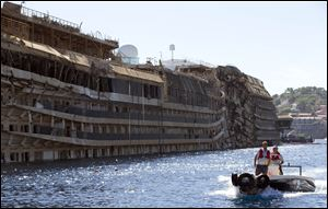 People take a small boat past the damaged side of he Costa Concordia  on the Tuscan Island of Giglio Sept. 18. The capsized ship was pulled upright in an operation the day before.