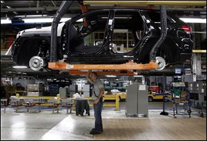 Jeff Caldwell, 29, right, a chassis assembly line supervisor, checks a vehicle on the assembly line at the Chrysler Jefferson North Assembly plant in Detroit.