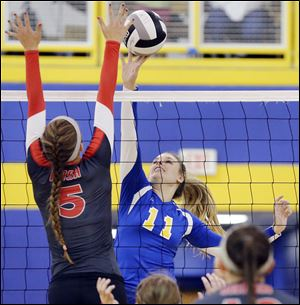 St. Ursula's Hannah Engler, right, attempts to spike the ball against Central Catholic's Sierra Sedlak on Thursday. The Arrows beat the Eagles in three games.