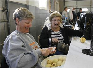 Valerie Rickenberg, left, and Mary Loeffler, both of Grand Rapids, cut up peeled apples for some of the thousands of pints of apple butter expected to be sold during the town's annual festival next month.