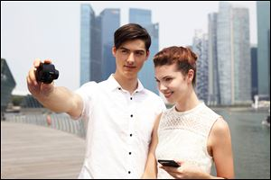 A couple use Sony's QX100 camera to take a photo of themselves. The camera offers a variety of features, from a real shutter button to stero microphones to a memory-card slot and more.
