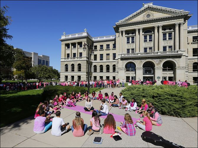 "CTY pink28p Senior Aria Machinski and eighth grader  Ross Thompson sing a song as Toledo School for the Arts surround the Lucas County Courthouse dressed in pink for ""Missing You Now That You're Gone"" breast cancer memories, Friday, September 27, 2013.   The Blade/Andy Morrison"