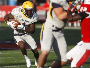 Toledo's Bernard Reddy (left) runs the ball past Ball State.