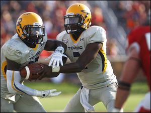 Toledo's Terrance Owens (right) hands the ball off to David Fluellen.