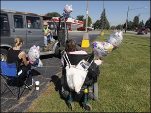 From left: Tiffany Jarosz, Sandy Kincaid and her daughter Rayvonna Kincaid wait in a parking lot on Coy Rd. with balloons in anticipation of releasing them during the passing of Elaina's funeral procession from the Eggleston Meinert & Pavley Funeral Home in Oregon, Ohio to the cemetery in Millbury.