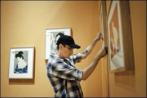 "Art Handler Timothy Gaewsky hangs a frame on a wall in preparation for the exhibit ""Fresh Impressions: Early Modern Japanese Prints"" at the Toledo Museum of Art. The exhibit is set to open on Oct. 4."
