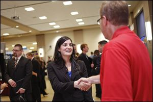 UT graduate student Sereen Jarouche shakes hands with Rick Mattingly of Marathon during the University of Toledo College of Business and Innovation fall job fair Friday.  Economists say part of the reason for the higher unemployment rate is that more people are looking for work.