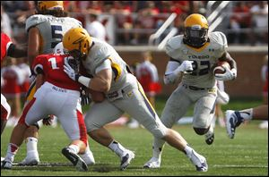 Toledo's David Fluellen (right) runs the ball up field past Ball State Universit.
