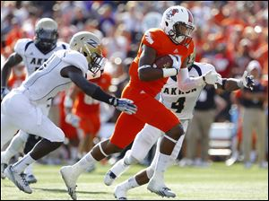 BG's Shaun Joplin, center, gets past Akron's Emmanuel Lartey, left, and Johnny Robinson to score a touchdown on Saturday.