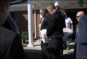 Terry Steinfurth Sr., grandfather of Elaina Steinfurth, and her father Terry Steinfurth Jr., right front, carry Elaina's casket to the hearse at the Eggleston Meinert & Pavley Funeral Home in Oregon, Ohio.