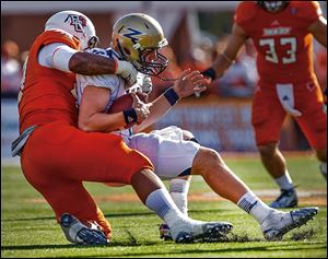 Bowling Green defensive end Bryan Thomas, left, sacks Akron quarterback Kyle Pohl during Saturday's game.