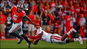 Ohio State quarterback Braxton Miller eludes Wisconsin's Warren Herring in Saturday's game. Miller threw for four touchdowns in his return from injury.