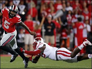 Ohio State QB Braxton Miller (5) eludes Wisconsin NG Warren Herring (45) during the first quarter.
