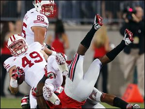 Ohio State SS C.J. Barnett (4) brings down Wisconsin TE Sam Arneson (49) during the first quarter.