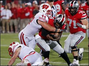 Ohio State QB Braxton Miller (5) is stopped by Wisconsin ILB Chris Borland (44) during the third quarter.