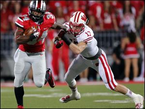 Ohio State TB Carlos Hyde (34)  runs the ball against  Wisconsin's Jack Russell (17) during the fourth quarter.