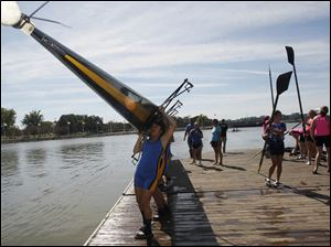 St. Ursula Academy crew member Hana Chung, 14, a ninth grader, and her teammates carry their boat after their race.