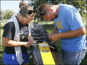 St. Ursula Academy assistant coach Cynthia Marley, left, and head coach Pete Fox, right, repair a broken rudder on one of the team's boats.
