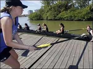 Haley Haxton, pulls the blade of an oar to pull a boat of Upper Arlington High School to the dock. Ninth grader Corinne Keefer, 14, right, is at the grip end of the oar.