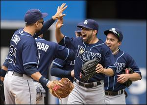 Tampa Bay Rays, from left, James Loney,  Matt Joyce, and Sam Fuld celebrate after beating the Blue Jays 7-6 on Sunday in Toronto.