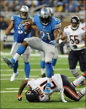 Lions running back Reggie Bush jumps over Chicago Bears strong safety Major Wright during an 37-yard touchdown run in the second quarter Sunday at Ford Field in Detroit. He ran for a season-high 139 yards on 18 carries.
