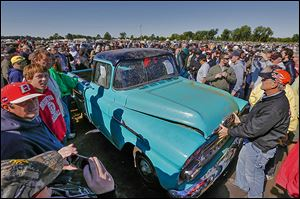 Crowds mill around a rare sky-blue, 1958 Chevy Cameo pickup driven 1.3 miles. It sold at the Lambrecht Chevrolet auction Saturday for $140,000.