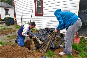 Volunteers John Gibbs and Carissa Curry remove remains from the backyard of a Luann Avenue home. The remains are suspected to be those of a missing dog that was linked to a New York murder.