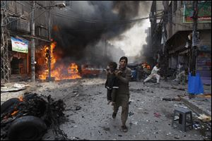 Pakistani men rush away from the site of a blast shortly after a car explosion today in Peshawar, Pakistan.